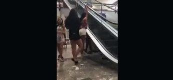 Elle s'accroche à l'escalator à l'extérieur et chute comme une grosse m****