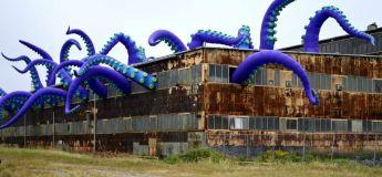 Une œuvre d'art urbain étonnante montre une pieuvre géante s'échappant d'un entrepôt