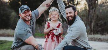 Les mignonnes photos de famille d'une fille et de ses deux papas