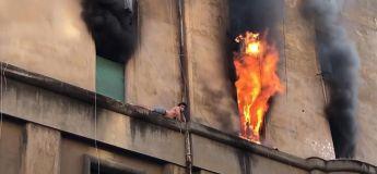 Un homme s'accroche au rebord étroit d'un immeuble en flammes pour échapper à l'incendie