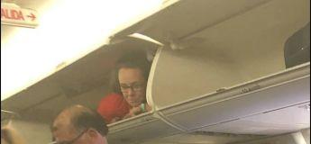Une hôtesse de l'air saute dans le compartiment à bagages en s'amusant