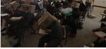 L'enseignant fait porter aux enfants des boîtes pour éviter la tricherie pendant l'examen