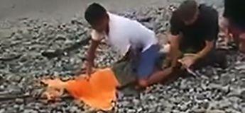 Un homme attrape un énorme crocodile à mains nues en se servant d'une serviette et d'un bout de ficelle