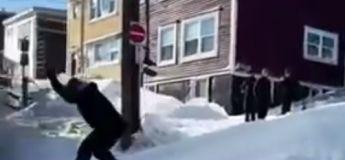 Un homme fait du snowboard en pleine ville après une forte tempête de neige