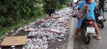 Des milliers de canettes de bière jonchent une route de Thaïlande après l'accident d'un camion de livraison