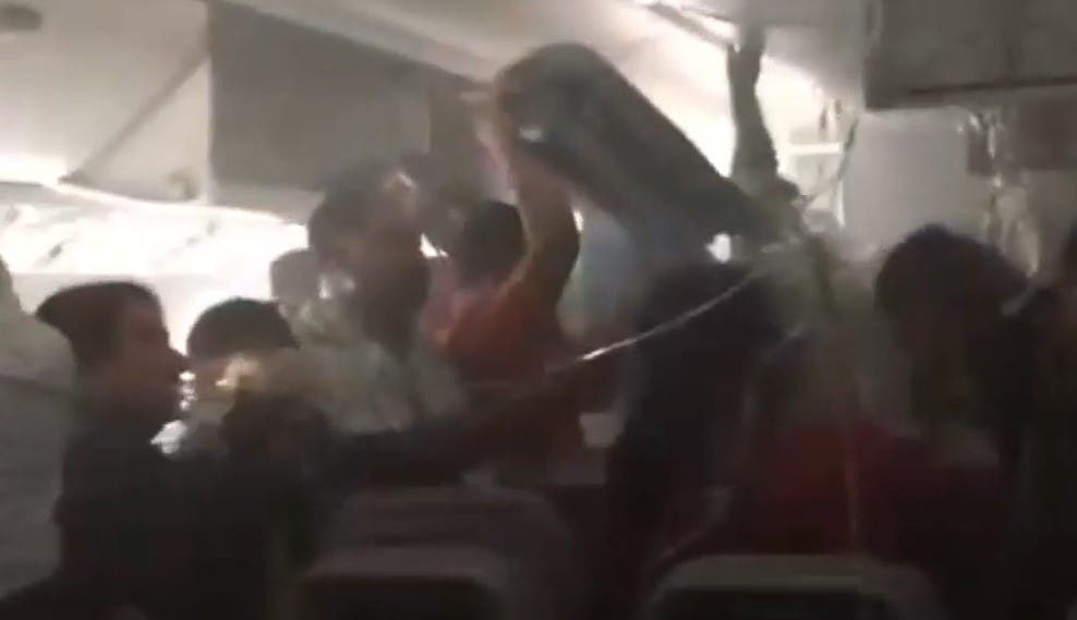 Après un crash d'avion, les passagers cherchent leurs bagages avant de sortir dans la précipitation