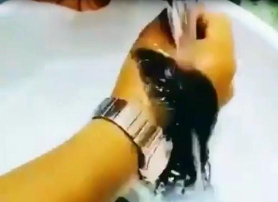De très longs poils poussent sur les mains de cet homme, et il s'en occupe comme une personne qui prend soin de ses cheveux longs