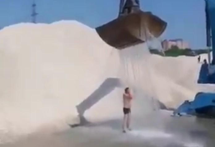 Cet homme prend une douche fraîche en se servant de la pince de son engin