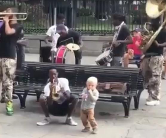 Ce petit garçon joue de la musique avec un orchestre de rue
