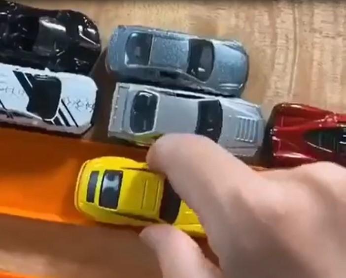 Cet homme teste les capacités des voitures de sport miniatures sur un circuit