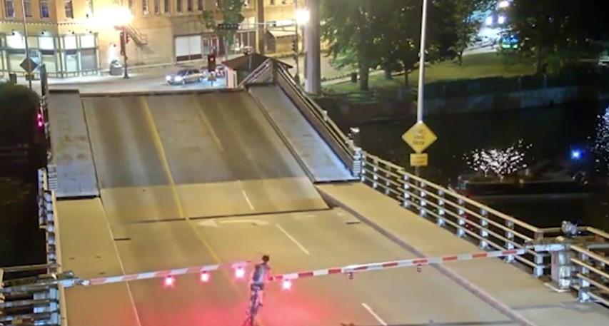 Cette cycliste persiste à traverser le pont malgré les barrières d'avertissement et tombe dans la brèche du pont-levis