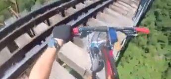 Ces cyclistes roule sur un pont ferroviaire sans remparts à quelques dizaines de mètres du sol