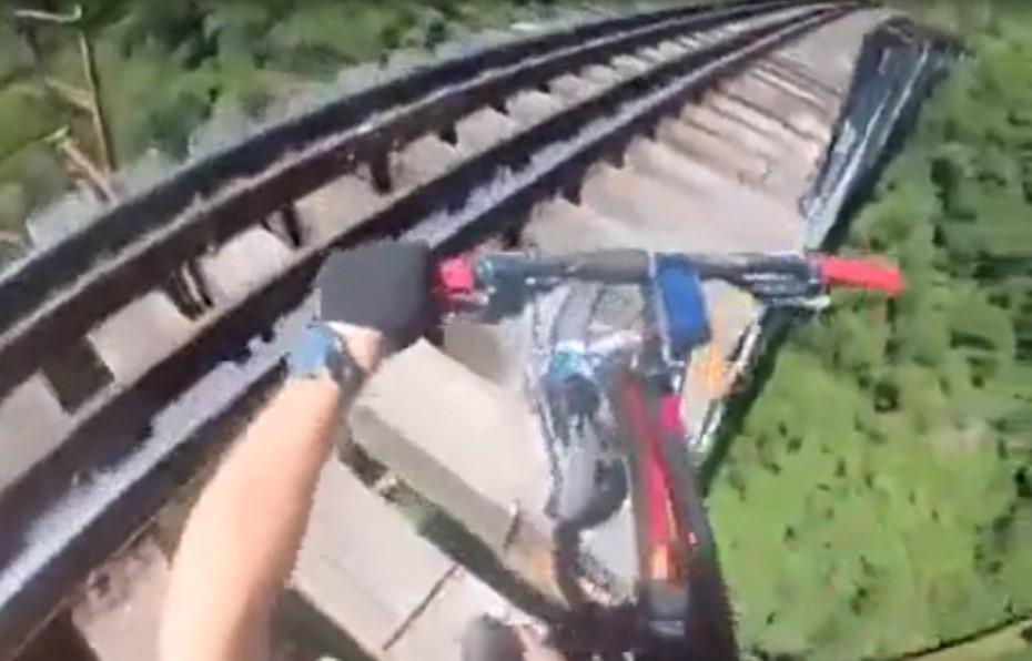 Ces cyclistes font une compétition sur un pont sans remparts à quelques dizaines de mètres du sol